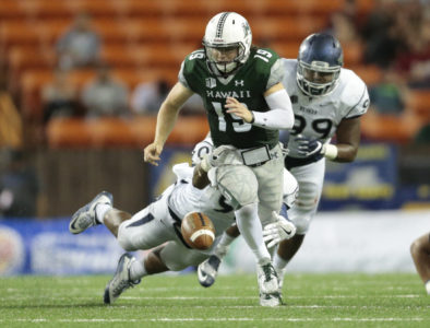 2016 October 1 SPT - HSA Photo by Jamm Aquino. Hawaii quarterback Dru Brown (19) fumbles the football after a hit from Nevada defensive end Malik Reed (90) and defensive end Korey Rush (99) during the second half of a college football game between the Hawaii Rainbow Warriors and the Nevada Wolf Pack on Saturday, October 1, 2016 at Aloha Stadium in Honolulu.  Hawaii won 38-17.