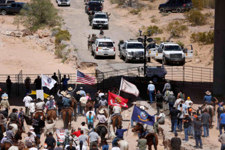 Protesters gather at the Bureau of Land Management's base camp, where cattle that were seized from rancher Cliven Bundy are being held, near Bunkerville, Nevada April 12, 2014. The U.S. Bureau of Land Management on Saturday said it had called off an effort to round up Bundy's herd of cattle that it had said were being illegally grazed in southern Nevada, citing concerns about safety. The conflict between Bundy and U.S. land managers had brought a team of armed federal rangers to Nevada to seize the 1,000 head of cattle. REUTERS/Jim Urquhart   (UNITED STATES - Tags: ANIMALS CIVIL UNREST AGRICULTURE CRIME LAW)